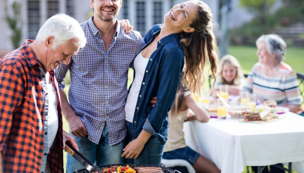 Couple and a senior man at barbecue grill preparing a barbecue in garden